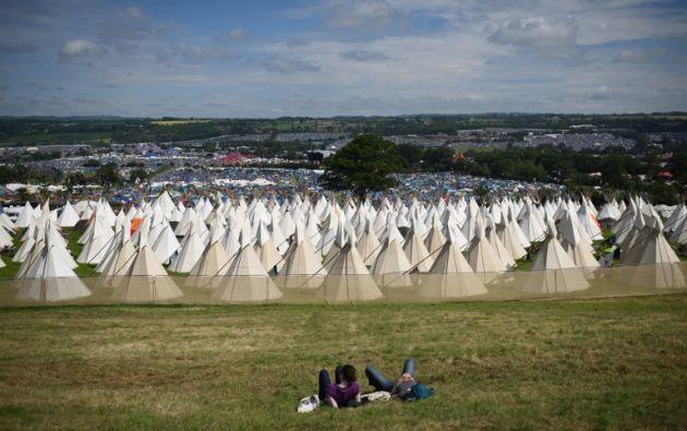 Juerguistas descansan sobre la hierba por encima de la zona de Tipi campo del Festival de Glastonbury de Música y Artes Escénicas en Worthy Farm.OLI SCARFF / AFP