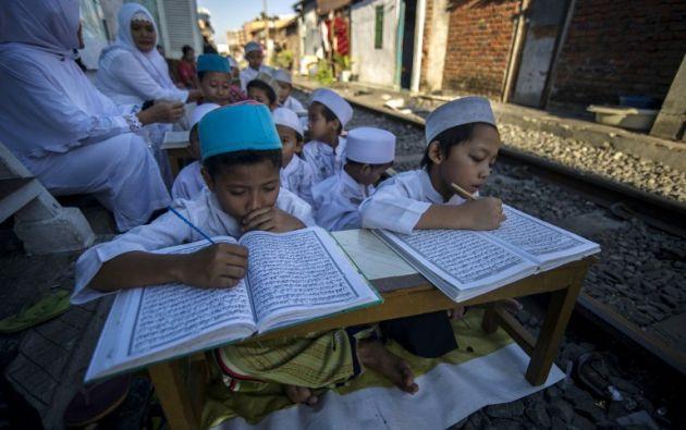 Niños musulmanes aprenden a leer el Corán junto a las vías del ferrocarril en Surabaya . JUNI KRISWANTO / AFP
