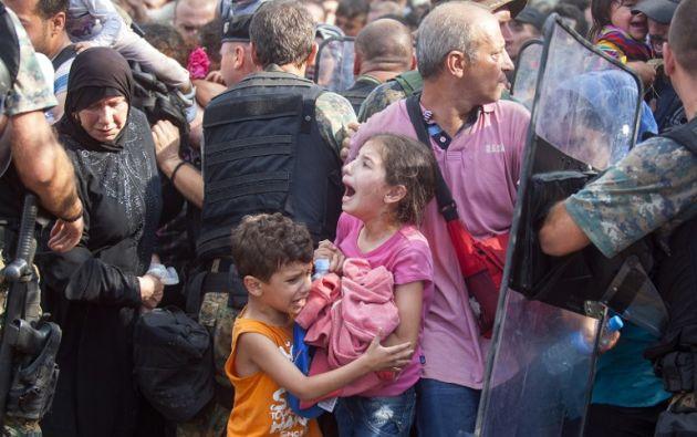 Una joven junto a un niño lloran mientras la policía bloquea un grupo de migrantes que intentan cruzar la frontera Macedonia. Foto: AFP