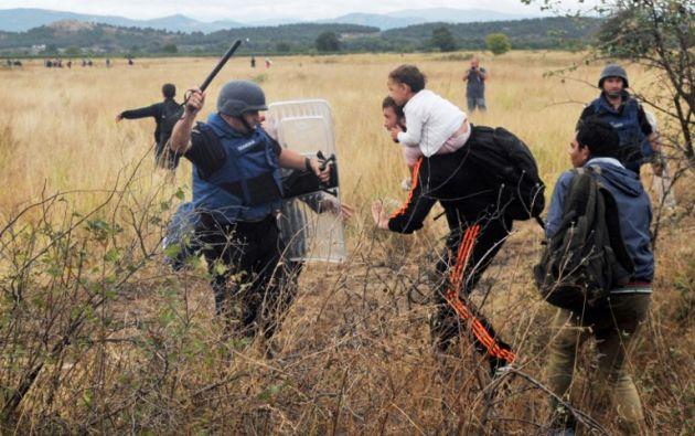 Un migrante trata de pasar una valla cerca de la ciudad de Idomeni, en la frontera entre Grecia y Macedonia. Foto: REUTERS