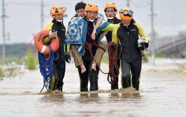 Un hombre es rescatado por los bomberos en una zona inundada por el río Kinugawa. Foto: REUTERS.
