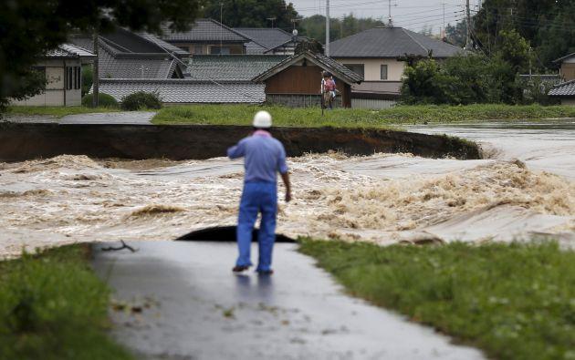 Un hombre observa las inundaciones en un descanso en el dique del río Kinugawa en una zona residencial. Foto: REUTERS.