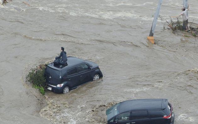 Personas esperan ser rescatadas en el techo de un coche y al lado de un poste de electricidad en una zona inundada por el río Kinugawa. Foto: REUTERS