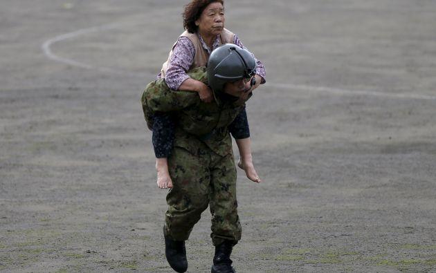 Una mujer es llevada por un miembro de JSDF después de ser rescatado por un helicóptero de una zona inundada. Foto: REUTERS.