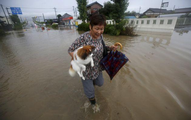 Una mujer camina a través de una zona residencial inundada por el río Kinugawa, cargando a su mascota. Foto: REUTERS.