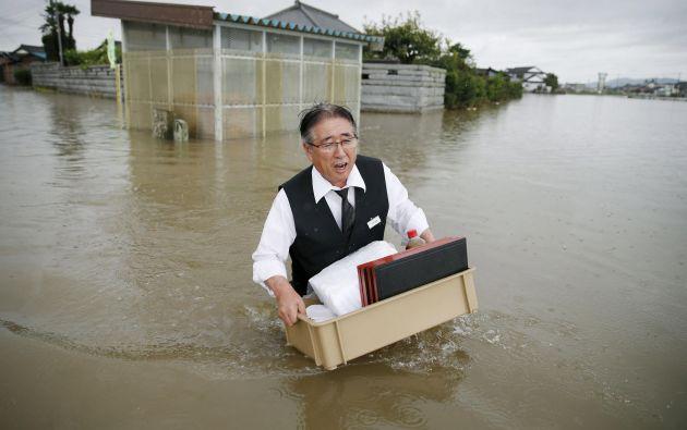 Un hombre sostiene una caja con sus pertenencias a través de una carretera inundada por el río Omoigawa. Foto: REUTERS.