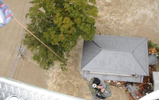 Un residente es rescatado por un miembro de la Fuerza de Autodefensa de Japón, elevandose hacia un helicóptero sobre una zona residencial inundada por el río Kinugawa. Foto: REUTERS.