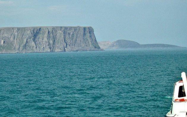 El cabo Norte (primer plano) situado en Noruega de Mageroya. Su acantilado, de 307 metros de altura, es considerado con frecuencia el punto más septentrional de Europa. Sin embargo, el vecino cabo Knivskjellodden (que se ve a la lejanía) se encuentra a 1.500 metros más al norte que el propio cabo Norte.