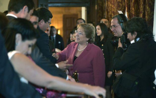 La presidenta chilena habla con los empleados del gobierno antes de su reunión con Correa. Foto: AFP.