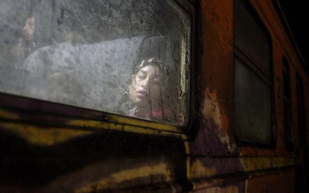 Una mujer descansa a bordo de un tren en dirección a Serbia, en un campo de tránsito para los refugiados Foto: Boris Grdanoski / AP