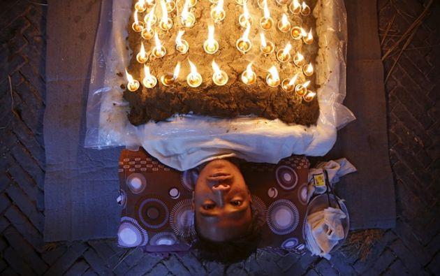 Un devoto se encuentra con lámparas de aceite en su cuerpo como parte de un ritual durante Dashain, festival hindú más grande del país Foto: Navesh Chitrakar / Reuters