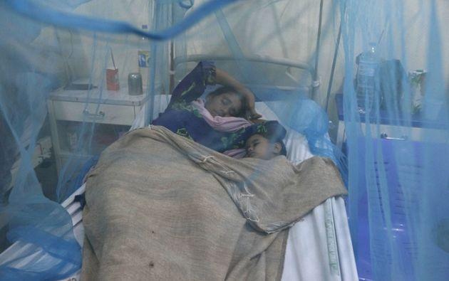 Una mujer duerme bajo un mosquitero con su hijo de dos años de edad, hijo, que tiene la fiebre del dengue Foto: Faisal Mahmood / Reuters