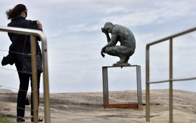 Un visitante toma una fotografía de una escultura del artista británico Laurence Edwards. AFP