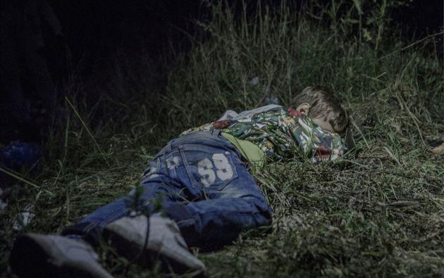 Ahmed, de 6 años de edad, Horgos, Serbia. Después de medianoche, cuando Ahmed se queda dormido en la hierba. Los adultos todavía están sentados alrededor, formulan planes para salir de Hungría sin registrarse con las autoridades.