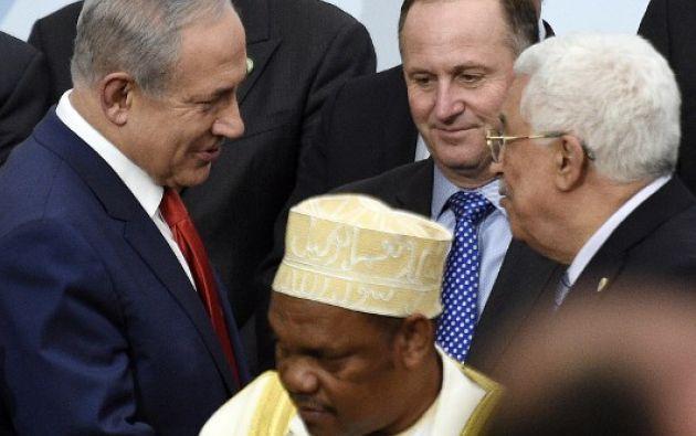 El primer ministro israelí, Benjamin Netanyahu (C, I) conversa con el presidente palestino, Mahmud Abbas (D) delante del presidente John Key de Nueva Zelanda (C) durante la foto familiar durante la COP21. AFP
