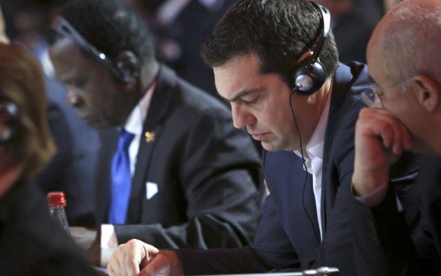El primer ministro griego Alexis Tsipras (C) escucha durante la ceremonia de apertura de la COP21. AFP