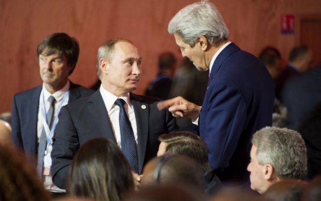 La secretaria de Estado estadounidense, John Kerry (D) habla con el presidente ruso Vladimir Putin (C) durante la ceremonia de apertura de la Conferencia Mundial de Cambio Climático. AFP