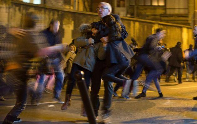 Un hombre carga dos niños mientras el pánico se desató entre los dolientes que pagaron su respeto en los lugares de los ataques terroristas en el restaurante Le Petit Cambodge y el Hotel Carillon en París. 15 de noviembre, 2015. Foto: Peter Dejong