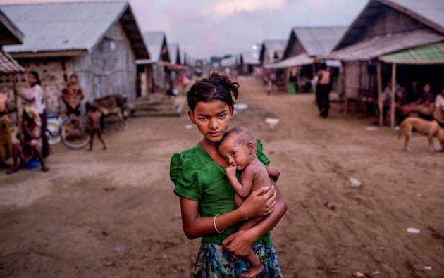 Oma Salema (12) sostiene a su hermano desnutrido Ayub Khan (1) en un campamento para rohingya en Sittwe, Myanmar. Foto: Tomas Munita
