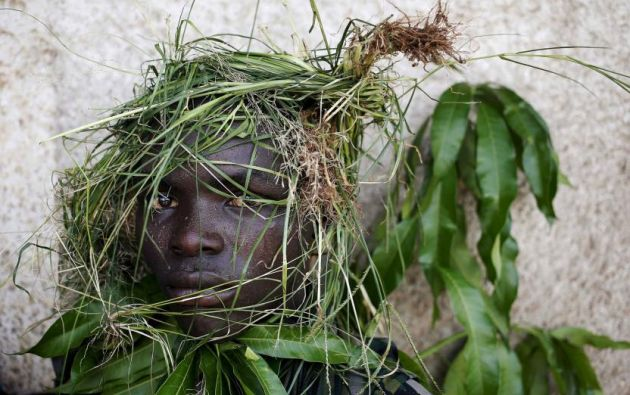 Un protestante se cubre con pasto para cubrir su identidad durante una protesta contra el intento del presidente Pierre Nkurunziza's para postularse por tercera ocasión en Bujumbura, Burundi. Mayo 11, 2015. REUTERS