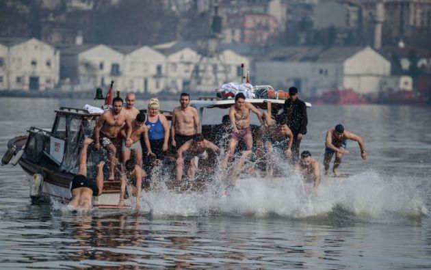 Nadadores ortodoxos griegos compiten para recuperar la cruz de madera desde el Bósforo río Cuerno de Oro, como parte de las celebraciones del día de la Epifanía en la iglesia de Fener. AFP