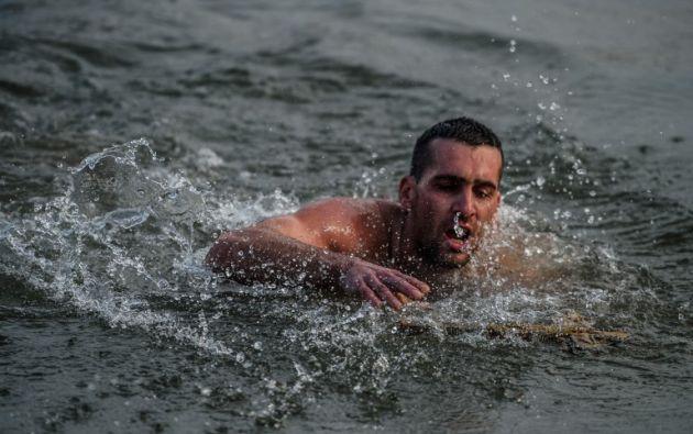 Nikolaos Solís intenta llegar a la cruz de madera recuperada  del río Bósforo, como parte de las celebraciones del día de la Epifanía. AFP