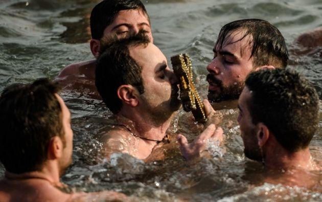 Un nadador sostiene una cruz de madera recuperada del río Bósforo Cuerno de Oro. AFP