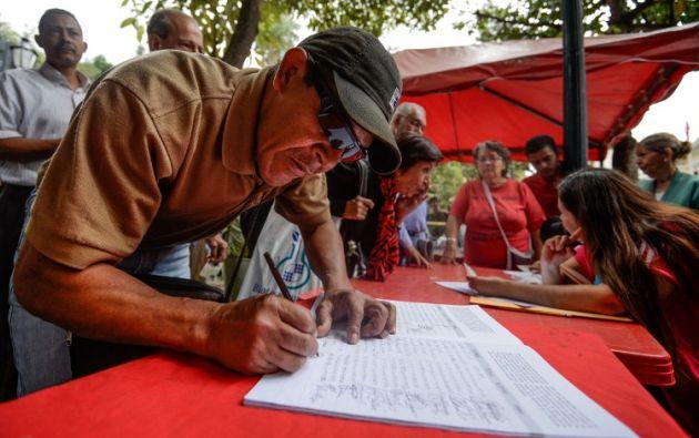 Venezolanos firmando en apoyo del Gobierno. Foto: AFP