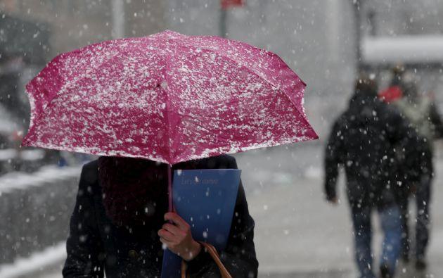 Una mujer usa un paraguas para evitar la caída de nieve en Manhattan. Foto: REUTERS