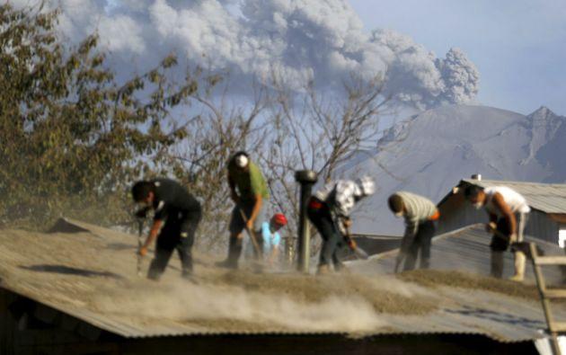 Varias personas limpian el techo en una casa de Ensenada, que quedó bajo las cenizas tras la primera erupción. Foto: REUTERS