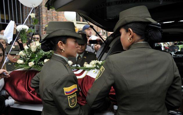 Dos policías cargan el ataúd de la pequeña Yuliana. Foto: AFP.