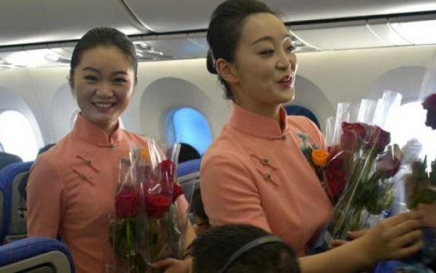 Azafatas de la aerolínea China Southern repartiendo las rosas ecuatorianas.| Foto: EFE.
