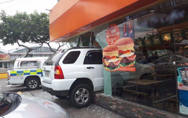 La conductora, aparentemente, al dar marcha al vehículo en lugar de retroceder, avanzó y se fue contra el local. Foto: cortesía