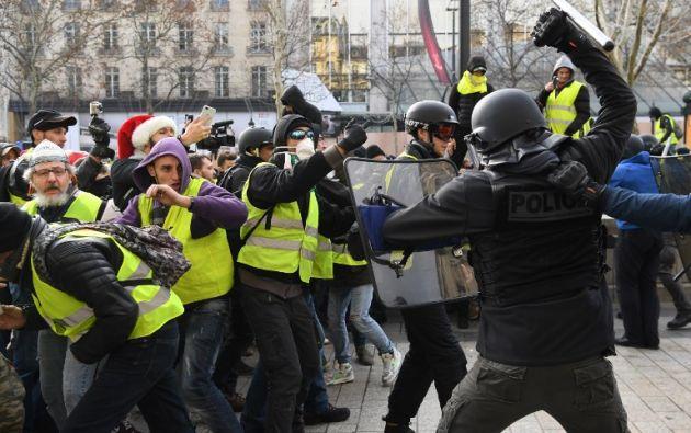 """La policía antidisturbios enfrentándose con hombres que visten """"chalecos amarillos"""". Foto: AFP"""