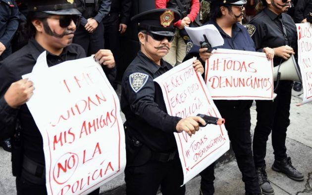 Manifestantes vestidas de policías reclaman justicia por la violación de una menor a manos de 4 uniformados. Foto: AFP.