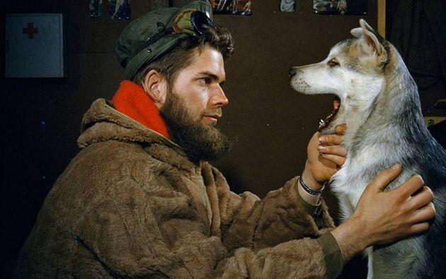 Hombre examinando los dientes de un cachorro de Malamute de 10 meses cerca del Polo Sur, 1957