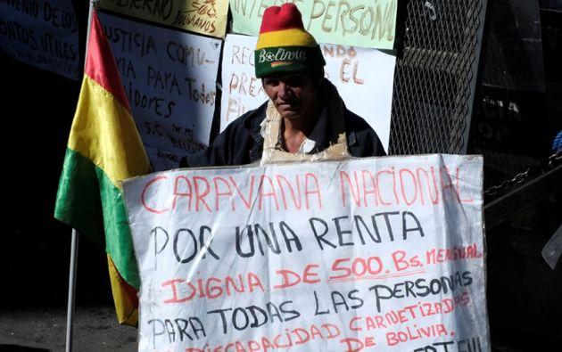 """Un hombre con discapacidad física sostiene una pancarta que dice """" caravana Nacional para un ingreso decente """" durante una protesta."""