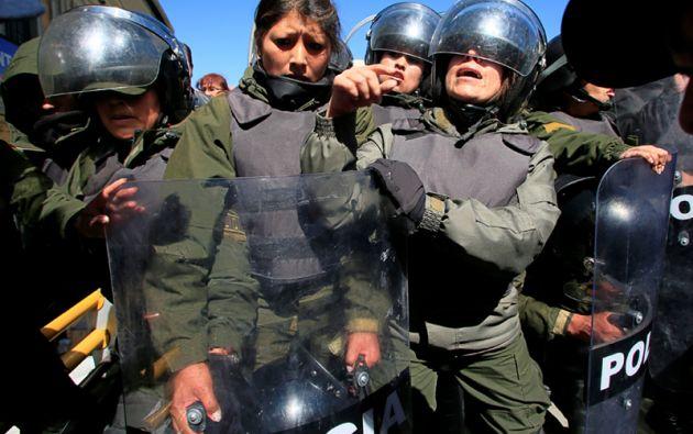 Policías antidisturbios tratan de impedir que los manifestantes con discapacidad física.
