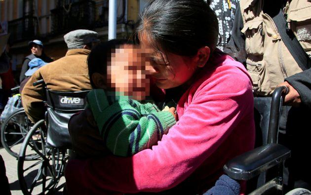 Una mujer discapacitada llora junto a su hijo en la protesta en demanda del subsidio por discapacidad.
