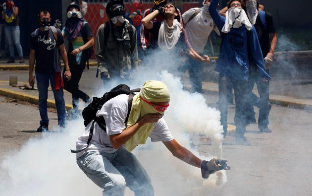 Un partidario de la oposición recoge un bote de gas lacrimógeno durante los enfrentamientos con las fuerzas de seguridad en una protesta contra el presidente Nicolas Maduro en Caracas