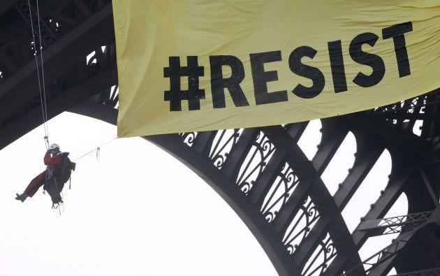 Activistas del grupo ecologista Greenpeace despliegan una bandera gigante frente anti-Nacional sobre la Torre Eiffel en París
