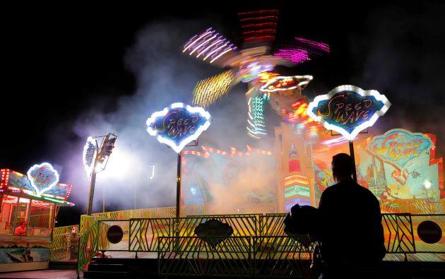 Un hombre observa a la gente montar una atracción en el parque de atracciones Prater en Viena, Austria