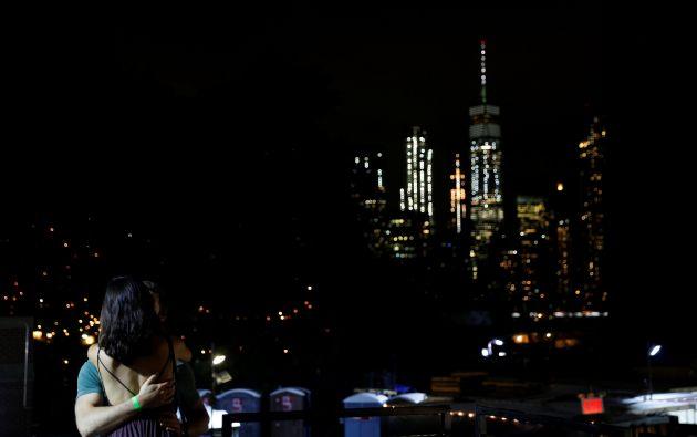 Dos personas se abrazan y se besan en el festival de fotografía de Photoville debajo del puente de Brooklyn frente al Bajo Manhattan, en la ciudad de Brooklyn de la ciudad de Nueva York, EE.UU