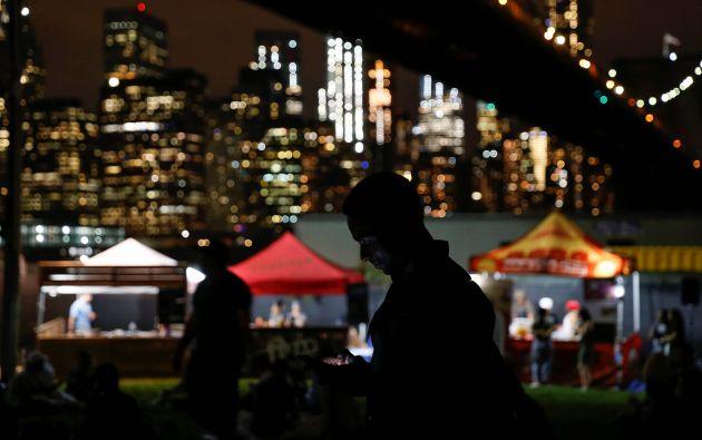 Un hombre usa su teléfono móvil cerca de puestos de comida en el festival fotográfico de Photoville debajo del puente de Brooklyn frente a Lower Manhattan, en la ciudad de Brooklyn de Nueva York, EE.UU