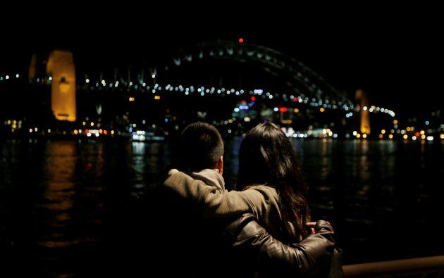Un abrazo de pareja como tomar en la vista del Sydney Harbour Bridge en Sydney, Australia