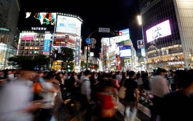 Los peatones caminan en un cruce de la cruce en el districto de las compras de Shibuya en Tokio, Japón