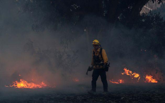 Un bombero trabaja para apagar los puntos calientes en un incendio forestal de movimiento rápido en Orange, California
