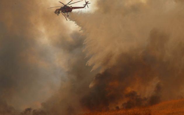Un helicóptero cae agua en un incendio forestal impulsado por el viento en Orange, California