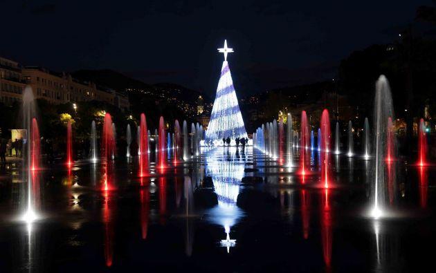 Árbol de Navidad iluminado y fuentes iluminadas en color se ven en Niza, Francia