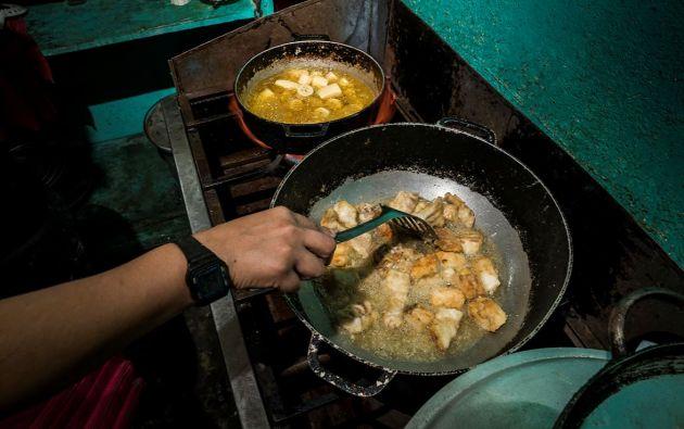 Una cocinera en el mercado de Puerto López, prepara un chicharrón de corvina.